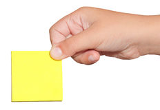 Mano que lleva a cabo una nota de post-it amarilla de la etiqueta engomada Imagen de archivo