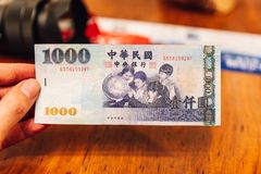 Mano que lleva a cabo una parte posterior del nuevo Taiw?n Dolla billete de banco de NT$1000 uno Thoundsan, para los turistas y e foto de archivo