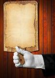Mano que lleva a cabo a una tabla de cortar de madera Imagen de archivo