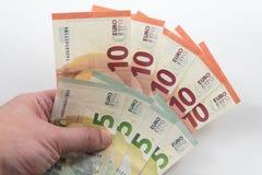 Mano que lleva a cabo 5 y 10 notas euro Imágenes de archivo libres de regalías