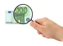 Mano que magnifica la nota del euro 100 Foto de archivo