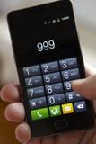 Mano que marca 999 en el teléfono móvil Fotos de archivo