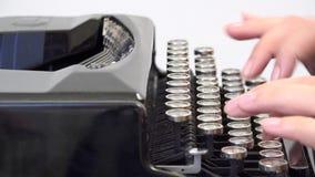 Mano que mecanografía en la máquina de escribir del vintage, cierre de la mujer encima del detalle metrajes