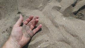 Mano que miente en día soleado de la arena imagen de archivo