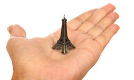 Mano que muestra una torre Eiffel minúscula Imagen de archivo