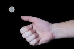 Mano que mueve de un tirón una moneda euro Imagen de archivo