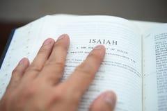 Mano que mueve de un tir?n la biblia en la paginaci?n de Isa?as Fotos de archivo