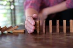 mano que para el efecto de continuo del dominó derribado la mujer protege foto de archivo