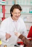 Mano que pasa el papel de la prescripción al farmacéutico Fotos de archivo libres de regalías
