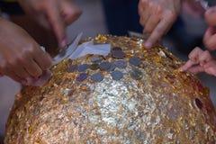 Mano que pega el cojín de oro en loknimit de piedra santo de la llamada de la esfera Fotos de archivo