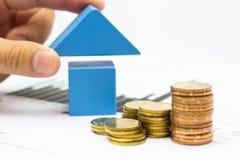 Mano que pone el tejado para el bloque de madera azul de la casa y el estado financiero con las monedas Fotografía de archivo libre de regalías