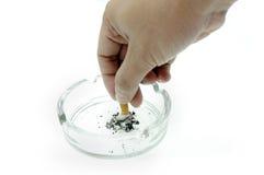 Mano que pone hacia fuera el cigarrillo en cenicero Foto de archivo