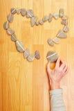 Mano que pone la piedra para querer el corazón Foto de archivo libre de regalías