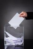Mano que pone la votación en caja Imagen de archivo libre de regalías