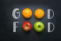 Mano que pone letras a la buena comida en la pizarra negra con las manzanas del rojo del verde de las naranjas de las frutas Ener fotografía de archivo libre de regalías