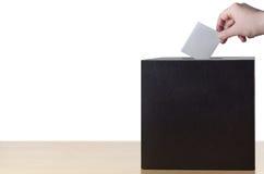 Mano que pone resbalón de votación en caja de la votación o de sugerencia Imagenes de archivo