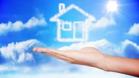 Mano que presenta diseño de la nube de la casa