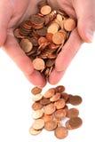 Mano que recoge monedas del centavo Imágenes de archivo libres de regalías