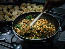 Mano que revuelve el curry indio del garbanzo y de la espinaca en wok en estufa de gas dentro fotografía de archivo