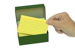 Mano que saca la tarjeta de índice brillantemente coloreado de la caja fotografía de archivo libre de regalías