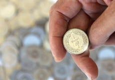 Mano que sacude una moneda imagen de archivo