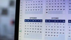 Mano que señala el fecha en la pantalla de la PC, el boleto de la reservación de la persona o el hotel por vacaciones almacen de metraje de vídeo