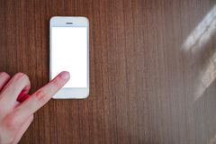 Mano que señala el finger en el smartphone con la pantalla blanca imagen de archivo