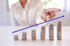 Mano que señala la pila creciente del dinero de aumento de las monedas foto de archivo