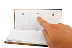 Mano que señala una fecha en calendario Fotos de archivo