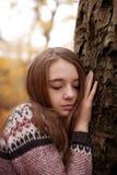 Mano que se inclina de la chica joven bonita contra un árbol Fotografía de archivo libre de regalías