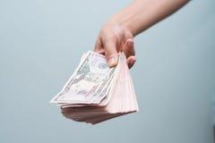 Mano que se sostiene con el dinero Imagen de archivo libre de regalías