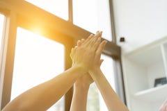mano que se une a del estudiante universitario joven, manos conmovedoras del equipo del negocio Foto de archivo