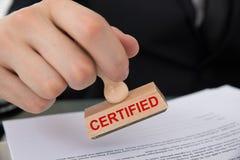 Mano que sella el documento con el sello de goma certificado Fotos de archivo