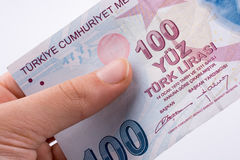 Mano que sostiene 100 billetes de banco de la lira de Turksh disponibles Fotos de archivo
