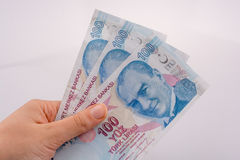 Mano que sostiene 100 billetes de banco de la lira de Turksh disponibles Imágenes de archivo libres de regalías