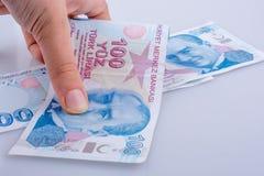 Mano que sostiene 100 billetes de banco de la lira de Turksh disponibles Foto de archivo libre de regalías