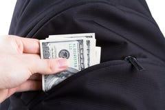 Mano que sostiene billetes de banco del dólar con la mochila Foto de archivo libre de regalías