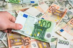 Mano que sostiene 100 billetes de banco euro Imágenes de archivo libres de regalías
