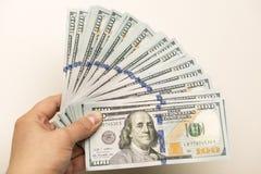 Mano que sostiene cientos billetes de banco del dólar Fotografía de archivo libre de regalías