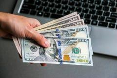Mano que sostiene cientos y cincuenta billetes de banco del dólar