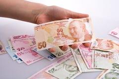 Mano que sostiene el billete de banco de la lira de Turksh disponible Foto de archivo