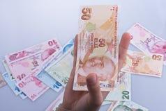 Mano que sostiene el billete de banco de la lira de Turksh disponible Imagen de archivo libre de regalías
