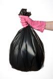 Mano que sostiene el bolso de basura fotos de archivo