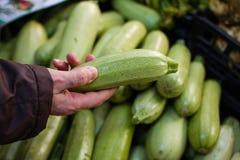 Mano que sostiene el calabacín en mercado Imagen de archivo