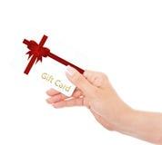 Mano que sostiene el carte cadeaux aislado sobre blanco Fotografía de archivo libre de regalías