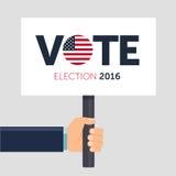Mano que sostiene el cartel Voto Elección presidencial 2016 en los E.E.U.U. Ejemplo plano Imágenes de archivo libres de regalías