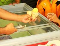 Mano que sostiene el cono de helado Fotos de archivo libres de regalías