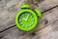 Mano que sostiene el despertador verde Imagen de archivo libre de regalías