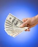 Mano que sostiene el dinero americano Imagenes de archivo