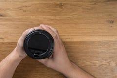 Mano que sostiene el envase de papel negro del café en fondo de madera imágenes de archivo libres de regalías